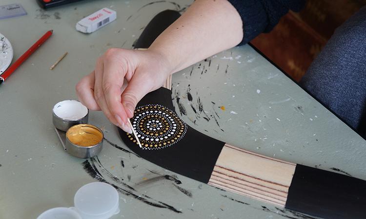Man Crafts: Artist decorating a handmade boomerang